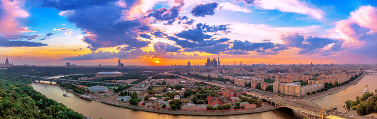 Wde angle vibrant panoramic view of sunset above Moscow city and cloud reflections in river with traveling boats and bridge Wall mural