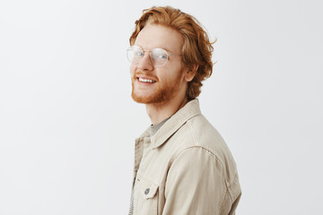 Studio shot of charming emotive and stylish redhead guy with beard in transparent glasses standing in profile to left and turning at camera with pleased joyful smile posing over gray background