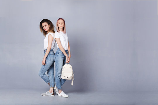 Full lenght shot of two charming girls standing over gray wall dressed in similar blue denim and white t-shirt prepare to pass all entrance examinations and become students in university or college