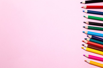 Seamless colored rainbow pencils row with wave on lower side, several arrangements, on pink paper. Concept of free space, copyspace, cover of notebook, album for drawing