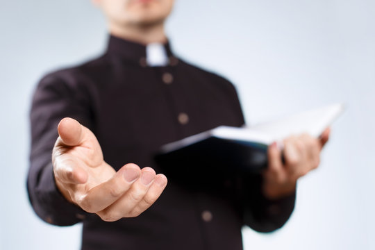 Young priest reading the Holy Bible and stretching his hand on neutral background