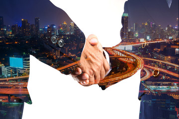 Businessman greeting Shakehand deal with Modern City shining at Night