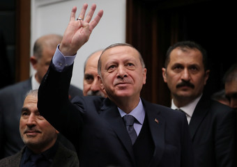 Turkish President Tayyip Erdogan greets members of parliament from his ruling AK Party as he arrives at a meeting at the Turkish parliament in Ankara