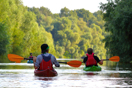 Group of friends (people) travel by kayaks. Kayaking together in wild Danube river and biosphere reserve in summer. Peacefull nature scene of calm river. Water tourism concept.