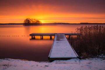 Sunrise over the Swiecajty lake and wooden footbridge near Wegorzewo, Masuria, Poland