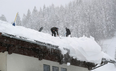Two men shovel snow on a rooftop during heavy snowfall in Filzmoos