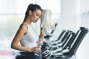 Woman tired and having rest after running on treadmill