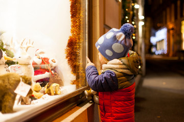 Kind schaut in Schaufenster mit Weihnachtsdekoration. Kid looking into christmas shopping window.