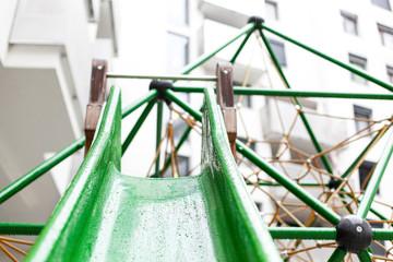Regentropfen auf nasser Rutsche am Spielplatz. Raindrops on wet skid on playground.