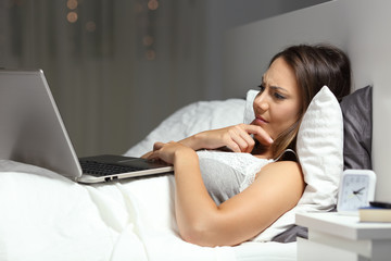 Confused woman using a laptop on the bed in the night