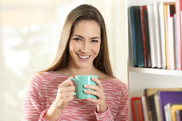 Happy woman holding a coffee cup looks at camera