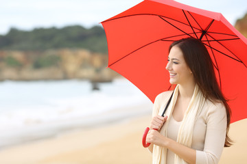 Happy woman looking away holding a red umbrella outdoors