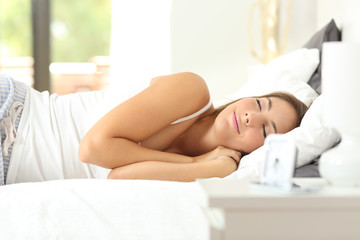 Happy woman sleeping deeply in a comfortable bed