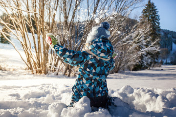 Kind spielt mit Schnee. Kid plays with snow.