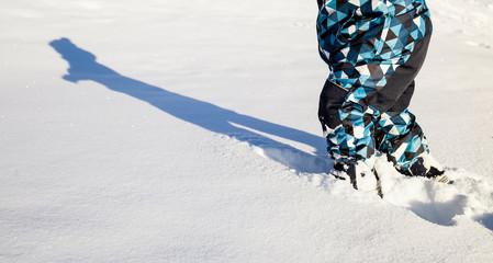 Kind läuft im Tiefschnee. Child walking in powder snow.