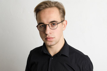 Man in shirt and glasses on white background.
