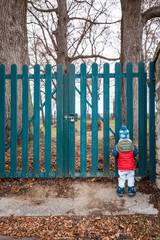 Child standing in front of closed garden gate. Kind steht vor geschlossenem Gartentor.