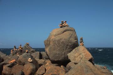 Veduta marina con rocce e sassi accatastati sullo sfondo del mare blu, Aruba, mar dei Caraibi