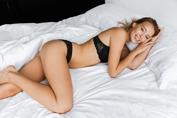 Young woman in lingerie underwear lies in bed at home.
