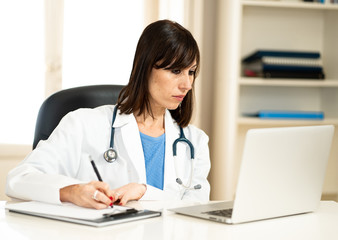 Female doctor working on medical expertise and searching information on laptop at hospital office