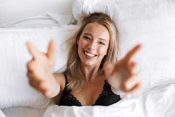 Beautiful young woman in lingerie underwear lies in bed at home raises hands to camera.