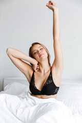 Beautiful young woman in lingerie underwear stretching at morning in bed at home.