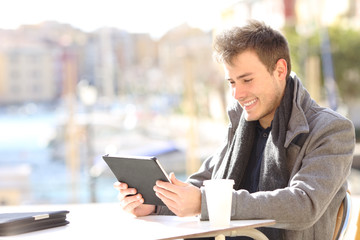 Happy man using a tablet in a coffee shop of a port