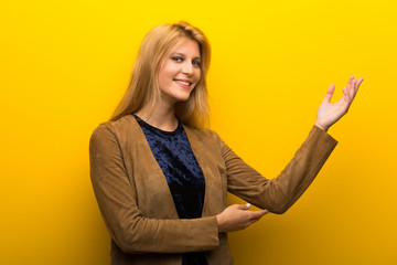 Blonde girl on vibrant yellow background extending hands to the side for inviting to come