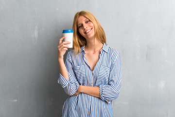Blonde girl holding hot coffee in takeaway paper cup on textured grunge wall background