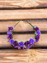 Handmade hoop purple flowers. Red and white hair band on wooden background. Top view