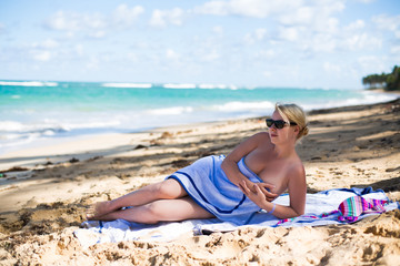 Young sexy blonde woman sunbathing near sea. Girl at the beach