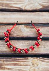 Handmade hoop Red  flowers. Red berries hair band on wooden background. Top view