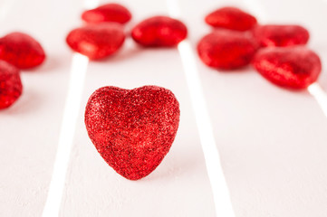 Many glitter red hearts on white wood background.