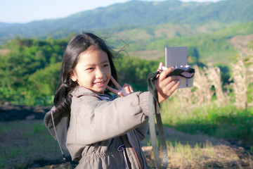 A little girl is taking a camera for selfie