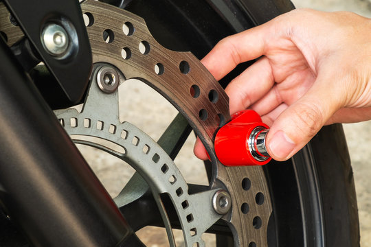 Man Using Motorcycle Disc Brake Lock to Secure His Motorcycle  form Thief
