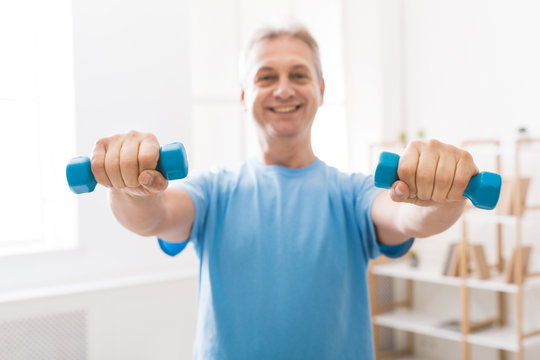 Mature man doing fitness training with dumbbells