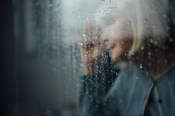 blurred portrait of lonely senior woman at home through window with raindrops