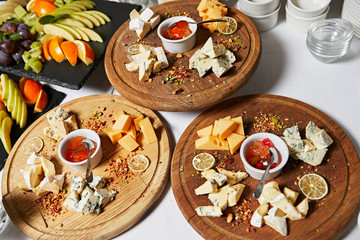 Cheese plate. Assortment of cheese with walnuts, almonds, grapes, figs, strawberries, blueberries and honey on a stone plate