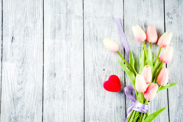 Valentine's day greetings postcard background, with tulips flowers and red heart, top view wooden background