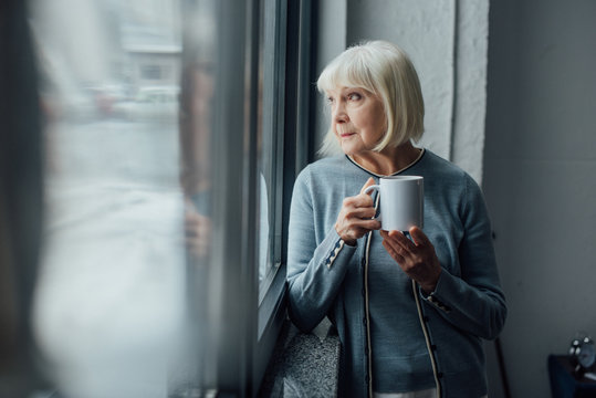 pensive senior woman holding cup of coffee and looking through window at home