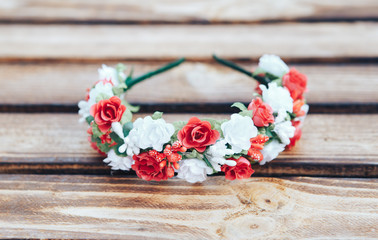 Handmade hoop red and white flowers. Red and white hair band on wooden background