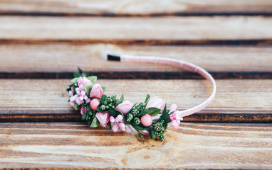 Handmade hoop flowers. Pink hair band on wooden background