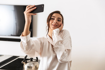 Photo of cheerful woman 20s wearing silk clothing taking selfie photo on black smartphone, while standing in kitchen in the morning
