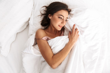 Image of beautiful woman 20s with dark hair smiling, while lying and sleeping in bed on white linen