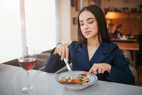 Nice young woman sit at table and eat salad. She hold both fork and knife. Model look down. Glass of red wine stand on table.