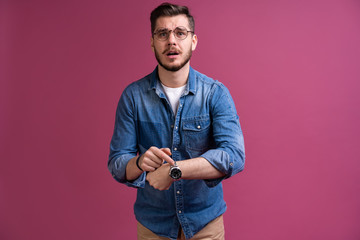 Portrait of a shocked man looking on wrist watch over pink background. Fototapete
