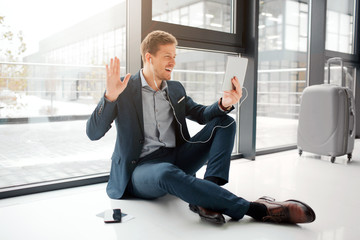 Cheerful young man sit on floor and greeting. He waves with ahnd. Young man has a video call. He uses headphones. Guy leaf suitcase and phone with tickets on floor.