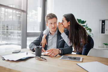 Young woman stand besides man and whispering on his ear. Guy listen to her and look at model. They are in meeting room together.