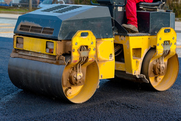 Worker leads the vibrating road roller to compact the asphalt laid out for the construction of a road