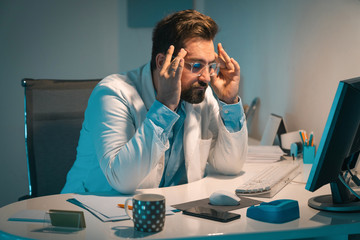 Exhausted doctor working late at office